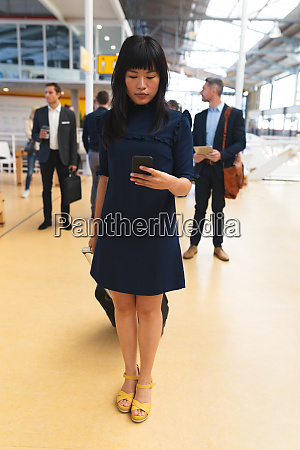 businesswoman using mobile phone while standing
