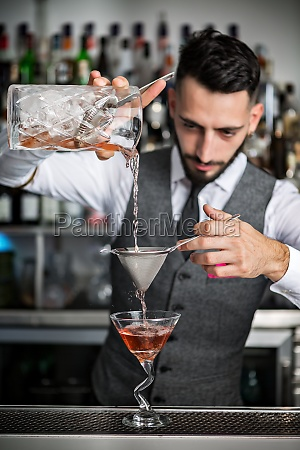 barman filling glass with cocktail